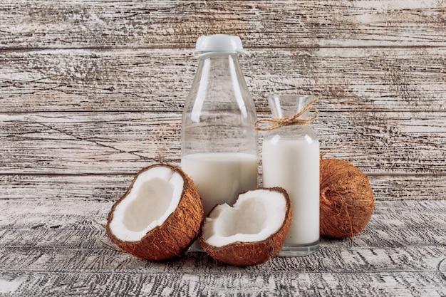 Algunas botellas de leche con dividido en medio coco en el fondo de madera blanco, vista lateral.