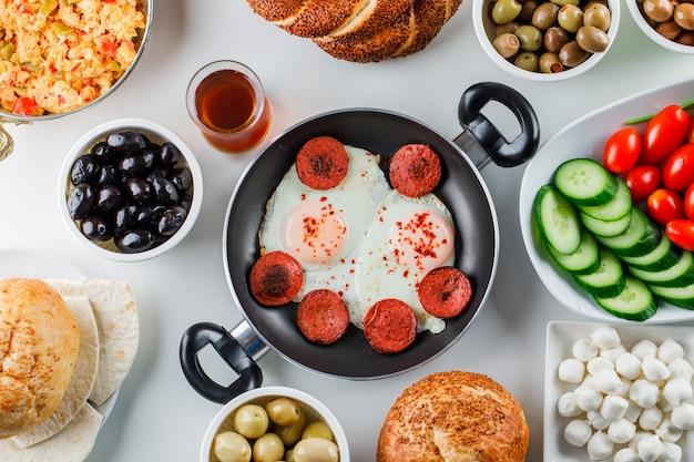 Algunas comidas deliciosas con ensalada, encurtidos, panecillos turcos, una taza de té en una sartén y una olla sobre una superficie blanca, vista superior