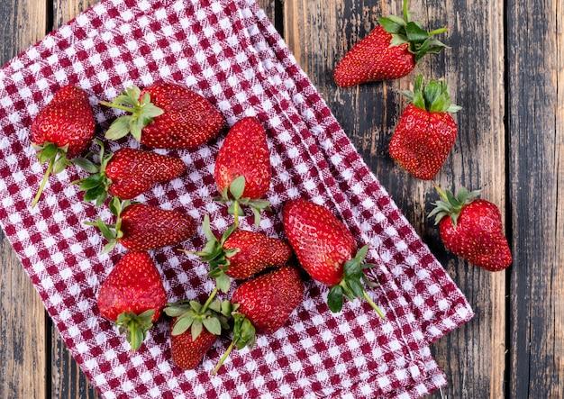 Algunas fresas en tela de picnic en la mesa de madera, aplanada.
