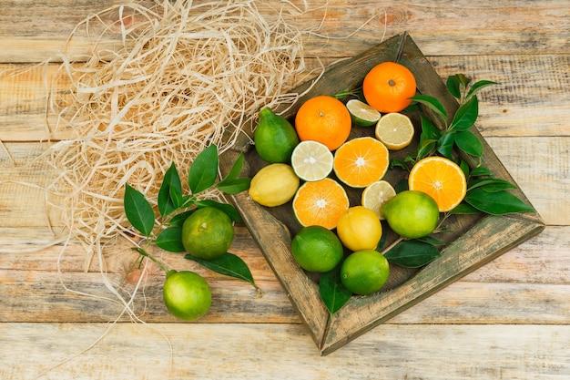 Algunas frutas cítricas en una placa de bronce sobre tabla de madera