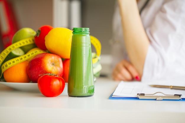 Algunas frutas como manzanas, kiwis, limones y bayas en la mesa de nutricionista
