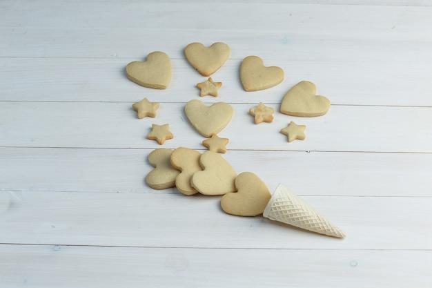 Algunas galletas con cono de galleta sobre fondo de madera, vista de ángulo alto.