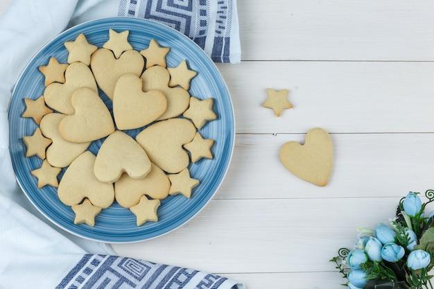 Algunas galletas con flores en un plato sobre madera y fondo de toalla de cocina, plano laical.