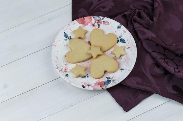 Algunas galletas en un plato sobre fondo de madera y textiles, vista de ángulo alto.