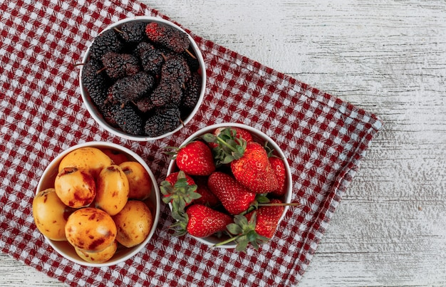 Algunas moras con fresas, nísperos en cuencos sobre tela y fondo de madera clara, vista superior.