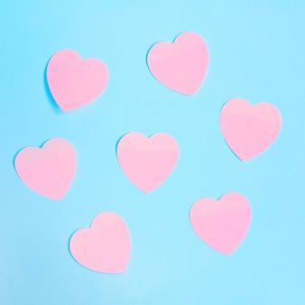 Algunas notas adhesivas de color rosa en forma de corazón sobre un fondo azul. día de san valentín, concepto de amor.