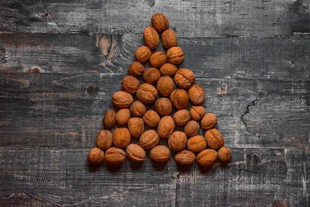 Algunas nueces en una vieja mesa de madera o superficie de madera están dispuestas en forma de árbol de navidad. vista superior del diseño