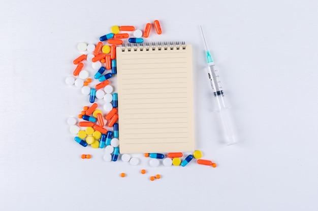 Algunas pastillas de colores con bloc de notas y aguja