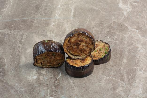 Algunas rodajas de berenjena fritas sobre mesa de mármol.