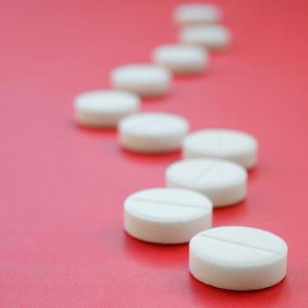 Algunas tabletas blancas se encuentran en una superficie de color rojo brillante. temas médicos y farmacéuticos.