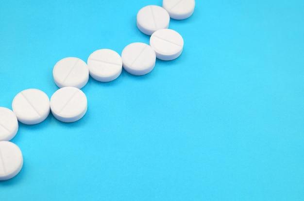Algunas tabletas blancas se encuentran en una superficie de fondo azul brillante