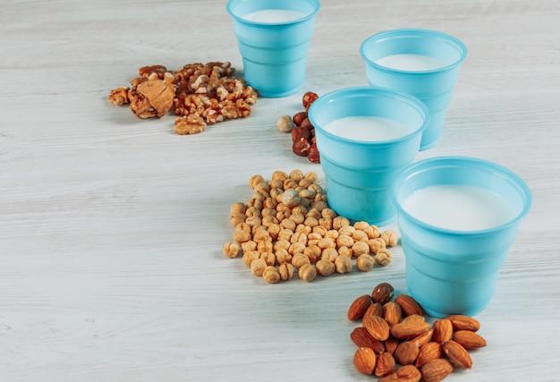 Algunas tazas de leche con avellanas, almendras y varias nueces sobre fondo blanco de madera, vista de ángulo alto.