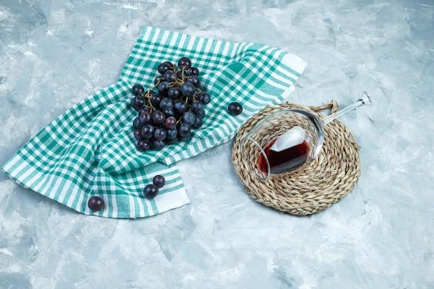Algunas uvas negras con una copa de vino, mantel sobre yeso y fondo de toalla de cocina, plano laical.