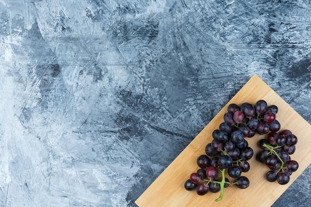 Algunas uvas negras sobre yeso sucio y fondo de tabla de cortar, endecha plana.