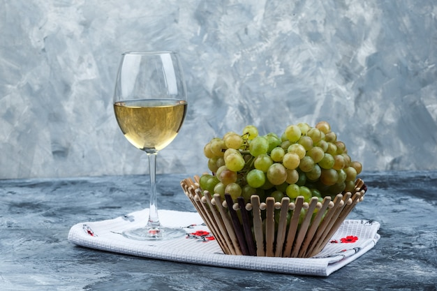 Algunas uvas verdes con copa de vino en una canasta sobre yeso sucio y fondo de toalla de cocina, vista lateral.