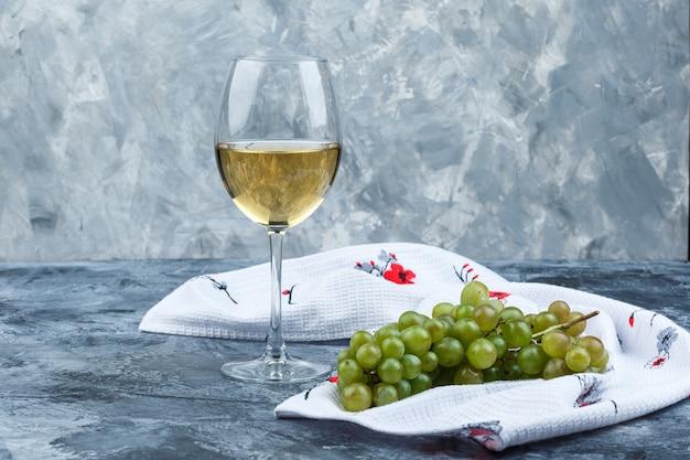 Algunas uvas verdes con una copa de vino sobre yeso sucio y fondo de toalla de cocina, vista lateral.