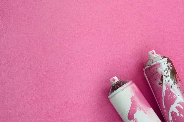 Algunos botes de aerosol de color rosa usados con gotas de pintura se encuentran en una manta suave