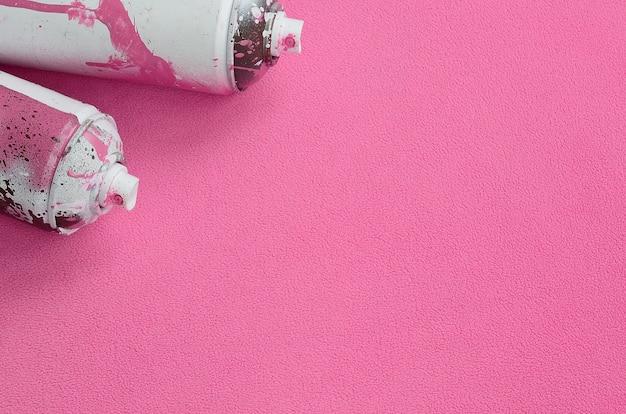 Algunos botes de aerosol rosados usados con gotas de pintura se encuentran.