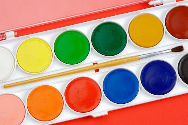 Algunos colores de pintura con el fondo rojo.