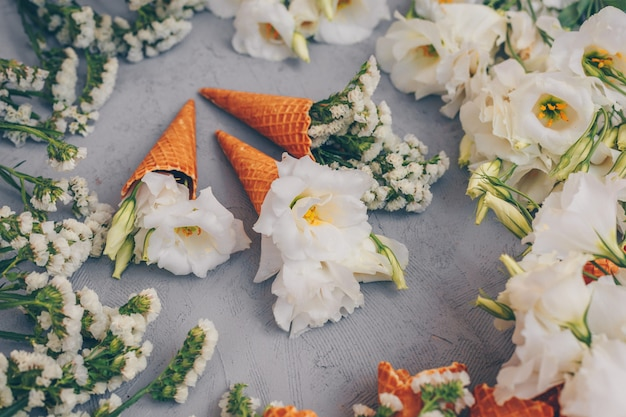 Algunos conos de helado con flores en gris claro, vista de ángulo alto.