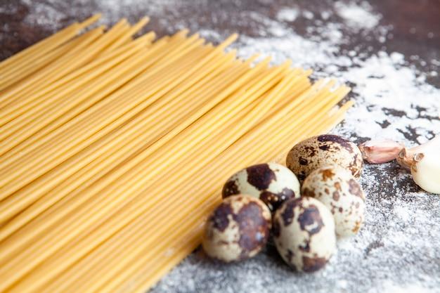 Algunos espaguetis con huevos y ajo sobre fondo oscuro con textura, vista de ángulo alto.