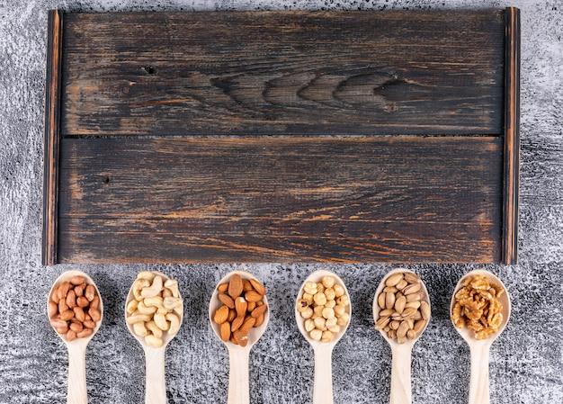 Algunos frutos secos variados y frutas secas con pacanas, pistachos, almendras, maní, en cucharas de madera sobre tabla de cortar de madera