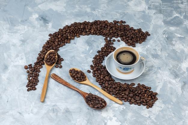 Algunos granos de café con bebida de café en taza y cucharas de madera sobre fondo de yeso gris, plano laical.