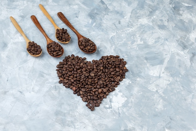 Algunos granos de café en cucharas de madera sobre fondo de yeso gris, plano laical.