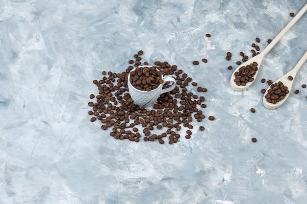 Algunos granos de café en taza blanca y cucharas de madera sobre fondo de yeso gris, vista de ángulo alto.