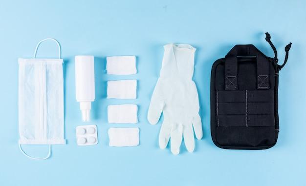 Algunos guantes médicos con bolso de mano, máscara, vendajes, spray alineados sobre fondo cian claro, vista superior.
