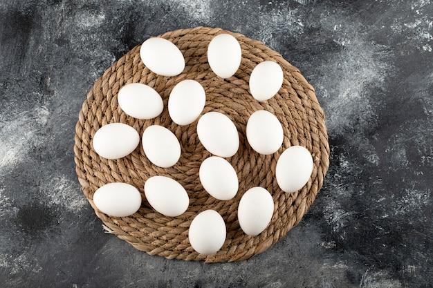 Algunos huevos de gallina cruda blanca sobre una tela de saco.