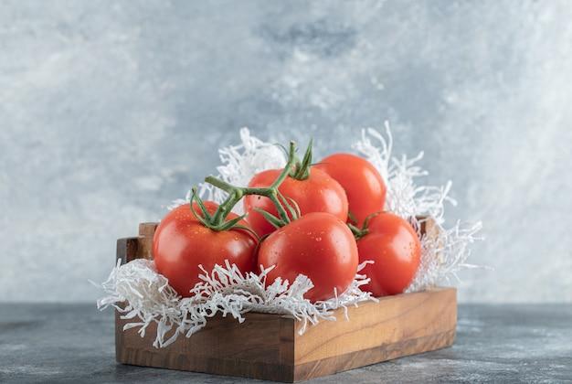 Algunos de jugosos tomates en canasta de madera.