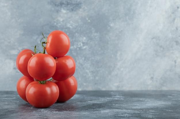 Algunos jugosos tomates en gris.