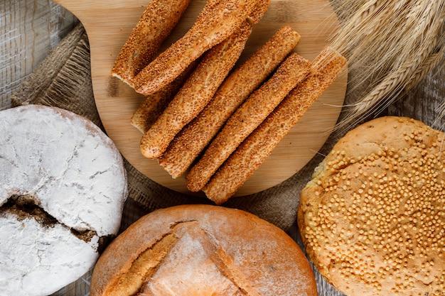 Algunos productos de panadería con cebada en la tabla de cortar y superficie de madera, vista desde arriba.