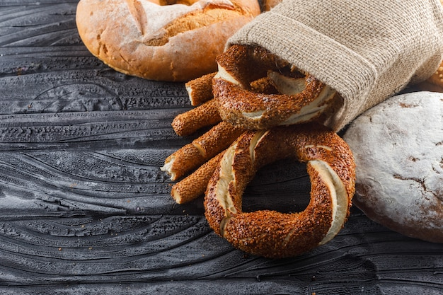 Algunos productos de panadería con pan, panecillos turcos en superficie de madera gris, vista de ángulo alto.