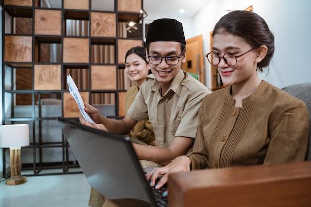 Algunos profesores con uniformes de funcionario trabajan en una computadora portátil y con el papeleo en casa
