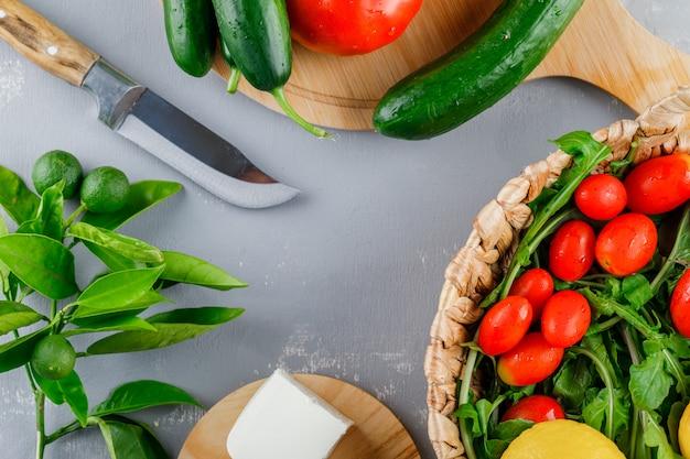 Algunos tomates con cuchillo, limón, pepino, queso, verduras en una tabla de cortar en superficie gris, vista superior
