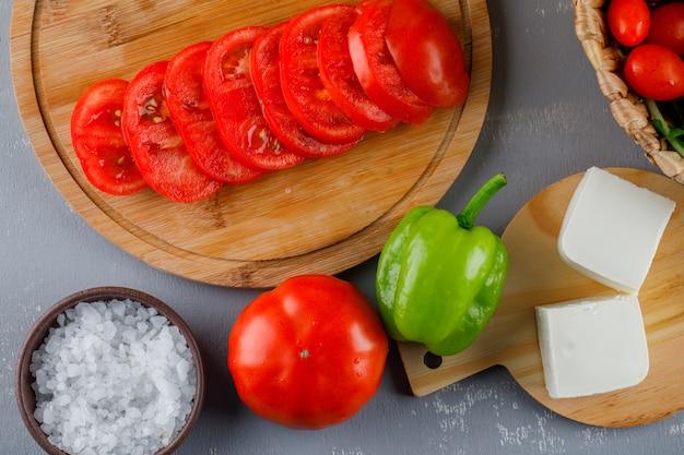 Algunos tomates en rodajas con queso, pimiento verde, sal en una tabla de cortar sobre una superficie gris, vista superior