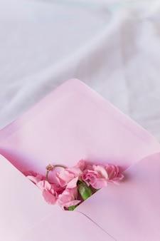Alianza de boda en sobre con flores brillantes.