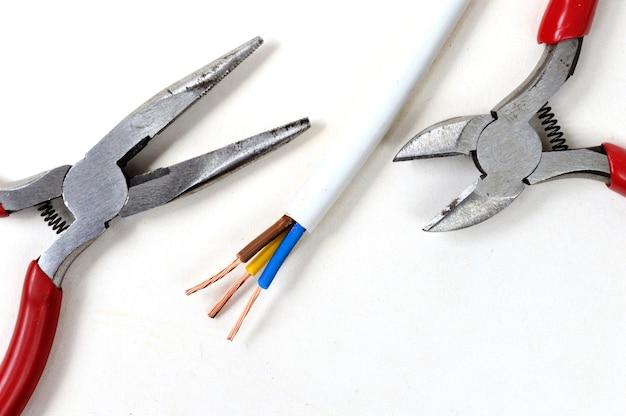 Alicates, alicates y alambre sobre un fondo claro. vista superior