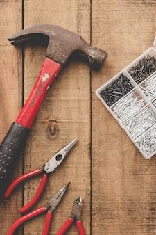 Alicates, martillo y organizador de uñas en mesa de madera. herramientas viejas copia espacio