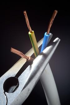 Los alicates sostienen cables eléctricos pelados. sobre un fondo negro. de cerca.