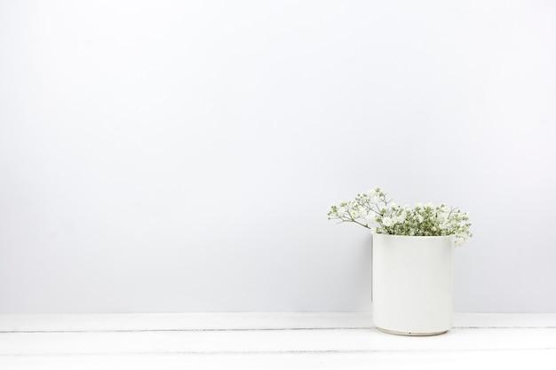 El aliento del bebé florece en un jarrón de cerámica sobre una mesa de madera blanca.