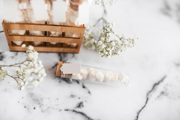 Aliento de bebé con flores y tubos de ensayo de malvavisco sobre fondo texturizado