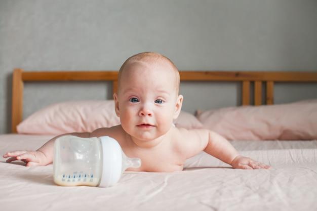 Alimentación artificial. el bebé se acuesta en la cama boca abajo y mira el biberón frente a él con la fórmula de leche adaptada