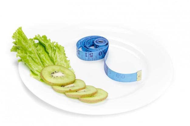 Alimentación saludable. cinta métrica y kiwi fresco