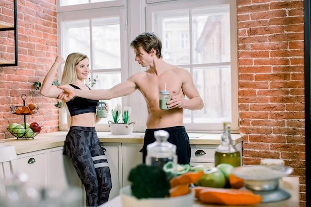 Alimentación saludable, estilo de vida físico, nutrición adecuada. pareja joven en ropa deportiva negra bebiendo batido verde en la cocina de su casa, chica bastante en forma flexionando sus bíceps