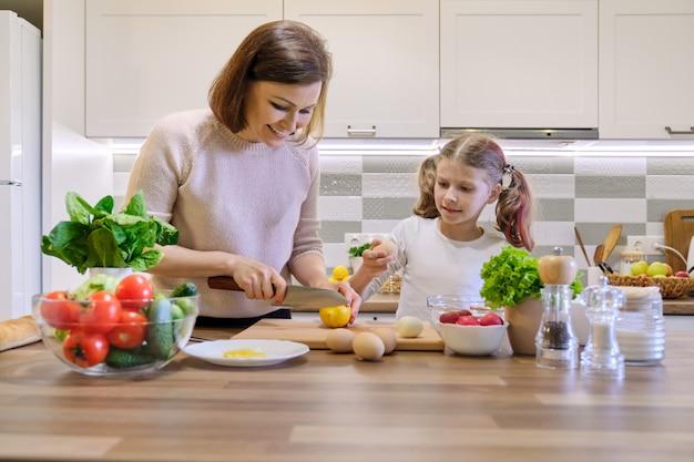 Una alimentación saludable, la madre enseña a la hija a cocinar