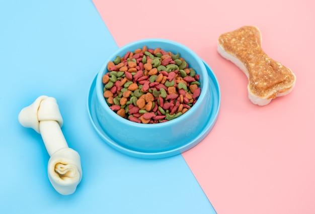 Alimento para mascotas con hueso de snack para perro o gato en superficie de color