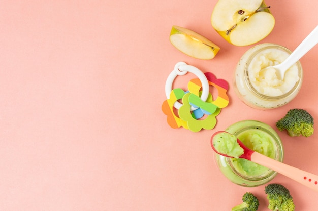 Alimentos para bebés en frascos sobre fondo rosa